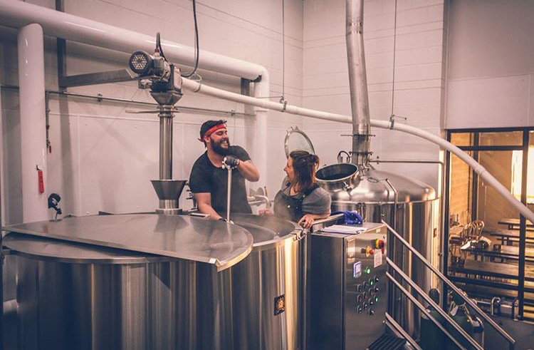 Candid photo of two individuals at Merit Brewing, sharing a laugh while brewing beer.