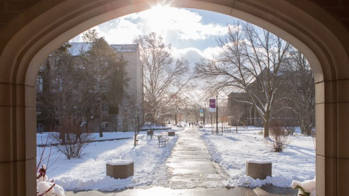 A view of campus looking out of the doorframe of the University Club in the winter.