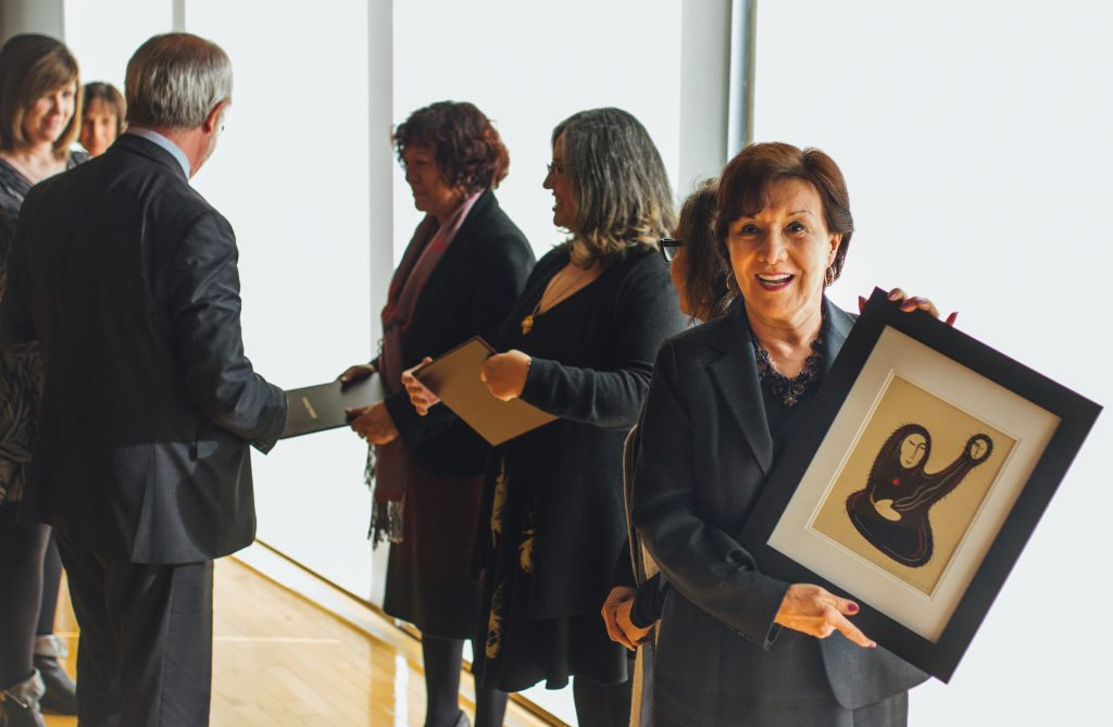 2018 President's Award Winner shows a picture while former President Patrick Deane speaks with recipients behind her.