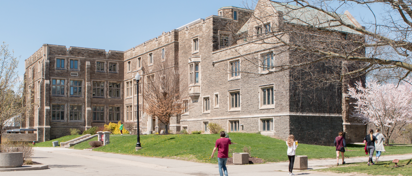 McMaster University's Hamilton Hall building in the spring, students walking, cherry tree blossoming.