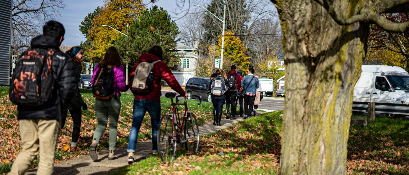Photograph of students walking in the fall down a sidewalk.