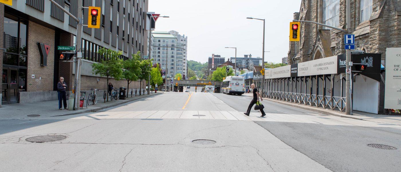 Photo of James Street North in Hamilton, Ontario. A person crosses the street, walking toward YMCA.